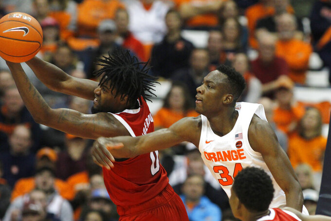 North Carolina State's D.J. Funderburk, left, and Syracuse's Bourama Sidibe, right, battle for a rebound in the first half of an NCAA college basketball game in Syracuse, N.Y., Tuesday, Feb. 11, 2020. (AP Photo/Nick Lisi)