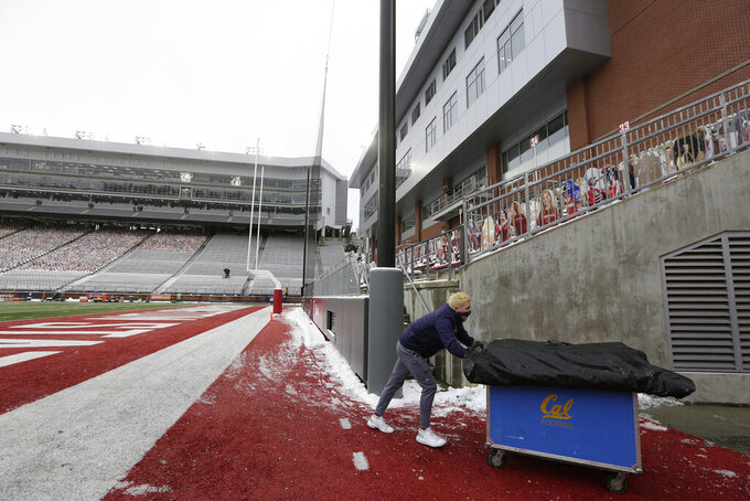 FILE - In this Dec. 12, 2020, file photo, California student equipment manager Will O'Connor removes equipment from Martin Stadium  in Pullman, Wash., after the NCAA college football game between Washington State and California was canceled because of a case of COVID-19 on the Cal team. In 2021, college football will attempt to return to normal after a season roiled by the pandemic while also adapting to a new paradigm in which the athletes have more power than ever before.  (AP Photo/Young Kwak, File)