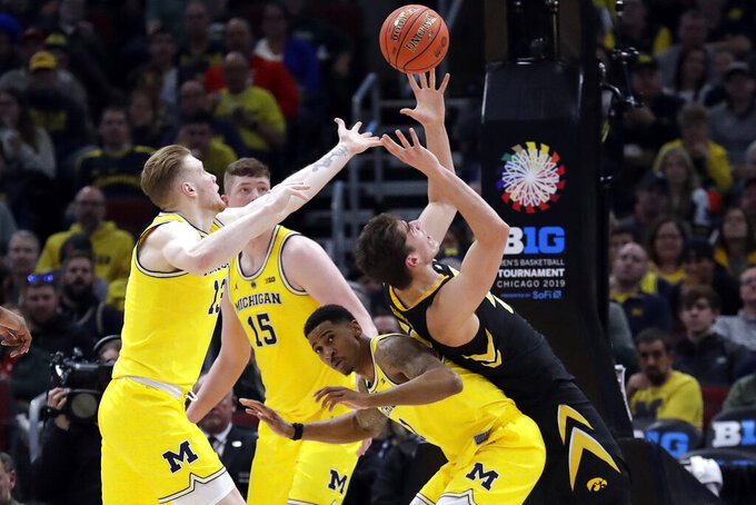 Iowa's Luka Garza tries to grab a rebound on top of Michigan's Charles Matthews (1) as Michigan's Ignas Brazdeikis (13) reaches for it during the second half of an NCAA college basketball game in the quarterfinals of the Big Ten Conference tournament, Friday, March 15, 2019, in Chicago. (AP Photo/Nam Y. Huh)