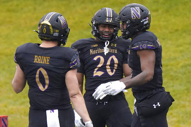 Northwestern wide receiver Kyric McGowan, right, celebrates with tight end John Raine, left, and running back Cam Porter after scoring a touchdown during the first half of an NCAA college basketball game against Illinois in Evanston, Ill., Saturday, Dec. 12, 2020. (AP Photo/Nam Y. Huh)