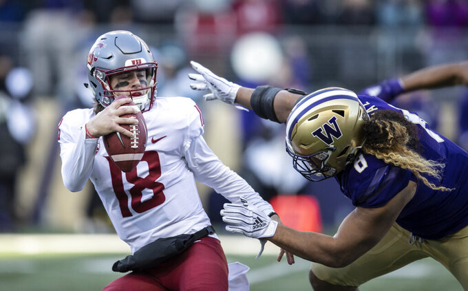 Washington State quarterback Anthony Gordon tries to escape the grasp of Washington defensive lineman Benning Potoa'e during the first half an NCAA college football game, on Friday, Nov. 29, 2019 in Seattle. (AP Photo/Stephen Brashear)