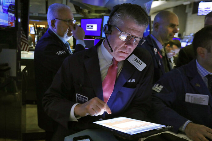 Trader Sean Spain, center, works on the floor of the New York Stock Exchange, Friday, Feb. 14, 2020. U.S. stocks wobbled between small gains and losses in early trading Friday as investors focused on another round of mostly solid corporate earnings. (AP Photo/Richard Drew)