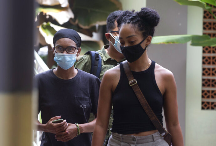 American graphic designer Kristen Antoinette Gray, left, walks with her partner Saundra Michelle Alexander, right, to be tested for the coronavirus at a hospital in Denpasar, Bali, Indonesia on Wednesday, Jan. 20, 2021. Gray, who arrived in Bali in January 2020 and wound up staying through the coronavirus pandemic, is being deported from the Indonesian resort island over her viral tweets that celebrated it as a low-cost, queer-friendly place for foreigners to live. (AP Photo/Firdia Lisnawati)