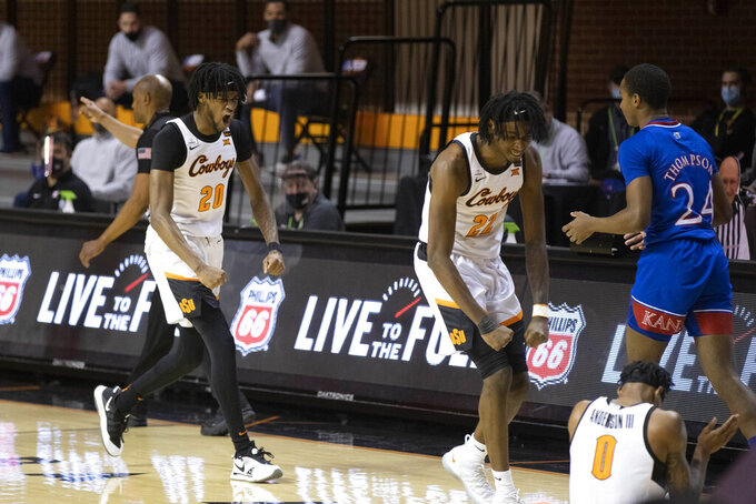 Oklahoma State's Keylan Boone (20) and Kalib Boone (22) celebrate during the first half of the team's NCAA college basketball game against Kansas in Stillwater, Okla., Tuesday, Jan. 12, 2021. (AP Photo/Mitch Alcala)