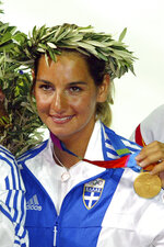 FILE - In this Saturday, Aug. 21, 2004 file photo, Greek 470 class skipper Sofia Bekatorou, displays her gold medal during the medal ceremony of the women's double-handed 470 dinghy sailing event at the 2004 Olympic Games in Athens, Greece. Olympic sailing champion Sofia Bekatorou of Greece has accused an unnamed sporting official of sexually assaulting her in 1998 during preparations for the Sydney Games. Bekatorou made the allegation Thursday Jan. 14, 2021 while speaking at an online event organized by the ministry of culture and sport. (AP Photo/Herbert Knosowski, file)