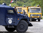Kosovo special police with armored vehicle stand near trucks where Kosovo Serbs block a road near the northern Kosovo border crossing of Jarinje, Monday, Sept. 20, 2021. Tensions soared Monday at the border between Kosovo and Serbia as Kosovo deployed additional police to implement a rule to remove Serbian license plates from cars entering Kosovo, while Serbs protested the move. (AP Photo/Bojan Slavkovic)