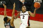 Georgia's Sahvir Wheeler (2) shoots while defended by Samford guard Richardson Maitre (14) during an NCAA college basketball game in Athens, Ga., Saturday, Dec. 12, 2020. (Joshua L. Jones/Athens Banner-Herald via AP)