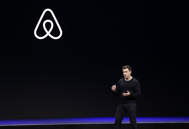 FILE - In this Feb. 22, 2018, file photo Airbnb co-founder and CEO Brian Chesky speaks during an event in San Francisco. In a world where social distancing has become a part of life and people are staying home in hopes of avoiding the coronavirus, companies that have built their business on the sharing economy are struggling. Ride-hailing companies are laying off thousands of employees as their once-loyal customers stay indoors. Those who venture out fear infection, and try to limit contact with others to minimize risk. And home-sharing apps such as Airbnb are slashing staff as the thought of opening living spaces to strangers begins to feel like an anachronism. (AP Photo/Eric Risberg, File)