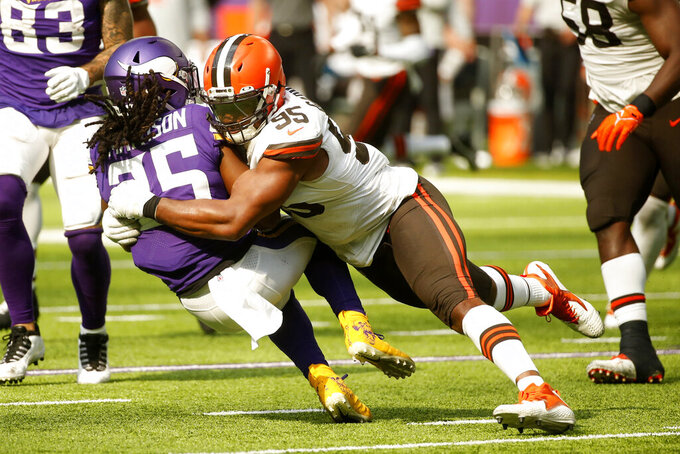 Minnesota Vikings running back Alexander Mattison (25) is tackled by Cleveland Browns defensive end Myles Garrett (95) during the second half of an NFL football game, Sunday, Oct. 3, 2021, in Minneapolis. (AP Photo/Bruce Kluckhohn)