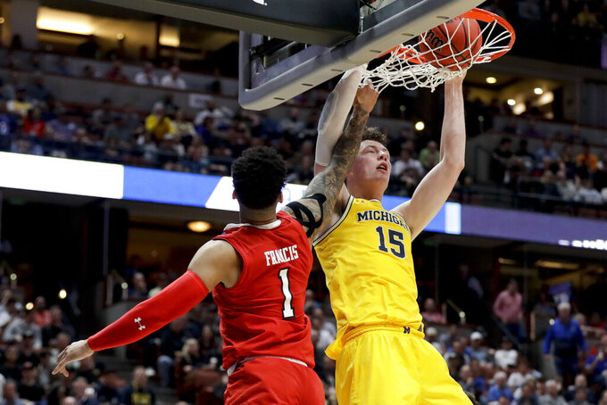 Michigan center Jon Teske dunks next to Texas Tech guard Brandone Francis during the first half an NCAA men's college basketball tournament West Region semifinal Thursday, March 28, 2019, in Anaheim, Calif. (AP Photo/Marcio Jose Sanchez)