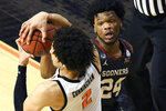 Oklahoma State guard Cade Cunningham (2) and Oklahoma guard Elijah Harkless (24) struggle for control of the ball during an NCAA college basketball game Monday, March. 1, 2021, in Stillwater, Okla. (AP Photo/Brody Schmidt)