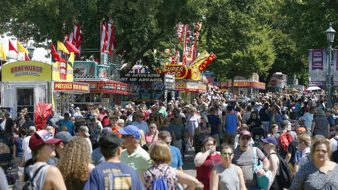 FILE - In this Aug. 22, 2019 file photo, thousands packed the Minnesota State Fair fairgrounds as the 12-day Fair got underway in Falcon Heights, Minn. Minnesota State Fair officials strongly urged fairgoers Wednesday, Aug. 18, 2021, to mask up both inside and outside but stopped short of imposing any mandates to fight the highly contagious delta variant of the coronavirus at the Great Minnesota-Get Together. The state fair opens Aug. 26, and runs through Labor Day. (AP Photo/Jim Mone,File)