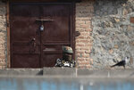 An Indian paramilitary soldier stands guard at a closed market area during a strike called by separatists in Srinagar, Indian controlled Kashmir, Saturday, Oct. 31, 2020. Kashmir's main separatist grouping called the strike to protest new land laws that India enacted on Tuesday, allowing any of its nationals to buy land in the region. Pro-India politicians in Kashmir have also criticized the laws and accused India of putting Kashmir's land up for sale. The move exacerbates concerns of Kashmiris and rights groups who see such measures as a settler-colonial project to change the Muslim-majority region's demography. (AP Photo/Mukhtar Khan)