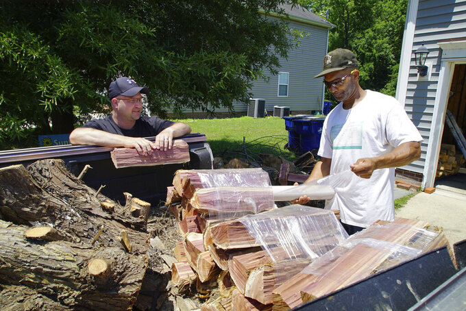"""Alton Lucas, right, wraps firewood for sale as he and neighbor Ryan Isaac, a correctional officer, chat outside Lucas' home outside of Raleigh, N.C., on Friday, June 18, 2021. """"I started the landscaping company, to be honest with you, because nobody would hire me because I have a felony,"""" said Lucas, whose business got off the ground with the help of Inmates to Entrepreneurs, a national nonprofit assisting people with criminal backgrounds by providing practical entrepreneurship education. (AP Photo/Allen G. Breed)"""