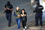 Georgian police officers escorts a woman who escaped from a bank where an armed assailant has taken several people hostage, in the town of Zugdidi in western Georgia, Wednesday, Oct. 21, 2020. An armed assailant took several people hostage at a bank in the ex-Soviet nation of Georgia on Wednesday, authorities said. The Georgian Interior Ministry didn't immediately say how many people have been taken hostage in the town of Zugdidi in western Georgia, or what demands the assailant has made. Police sealed off the area and launched an operation