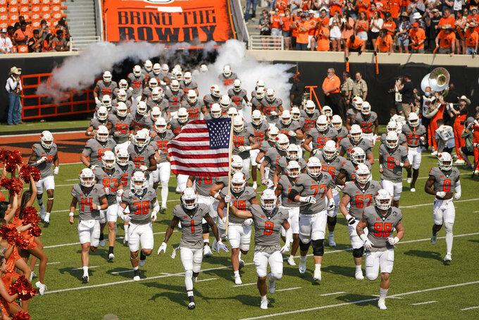 The Oklahoma State team runs onto the field before an NCAA college football game against Tulsa,, Saturday, Sept. 11, 2021, in Stillwater, Okla. (AP Photo/Sue Ogrocki)