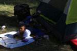 A boy lies with a coloring book outside a tent inside the sports complex where thousands of migrants have been camped out for several days in Mexico City, Friday, Nov. 9, 2018. About 500 Central American migrants headed out of Mexico City on Friday to embark on the longest and most dangerous leg of their journey to the U.S. border, while thousands more were waiting one day more at a massive improvised shelter.(AP Photo/Rebecca Blackwell)