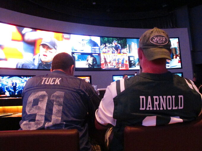 FILE: This Sept. 9, 2018 file photo shows football fans waiting for kickoff in the sports betting lounge at the Ocean Casino Resort in Atlantic City, N.J. A report released Feb. 2, 2021 by the American Gaming Association predicts fewer Americans will bet on this year's Super Bowl, a decrease driven largely by fewer people back at work in offices where betting pools are circulated. But the report also predicts a record amount will be wagered online this year. (AP Photo/Wayne Parry, FILE)