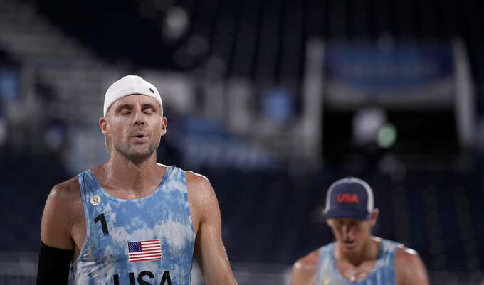 Jacob Gibb (1) and Tri Bourne (2) of the United States react after losing a point to Germany during a men's beach volleyball match at the 2020 Summer Olympics, Monday, Aug. 2, 2021, in Tokyo, Japan. (AP Photo/Felipe Dana)