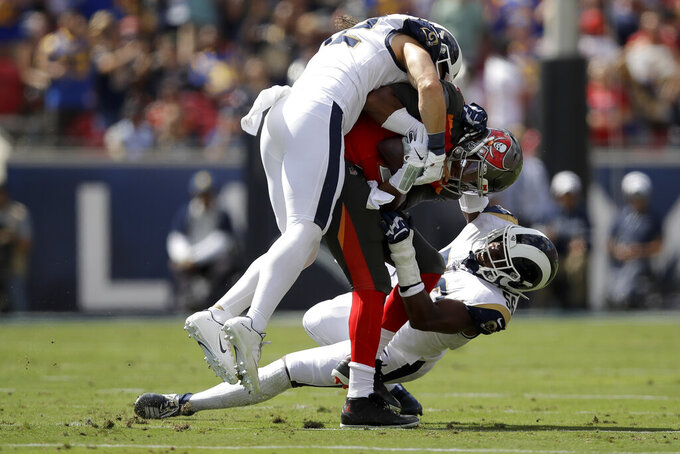 Los Angeles Rams outside linebacker Clay Matthews, top, and defensive end Dante Fowler sack Tampa Bay Buccaneers quarterback Jameis Winston during the first of an NFL football game Sunday, Sept. 29, 2019, in Los Angeles. (AP Photo/Marcio Jose Sanchez)