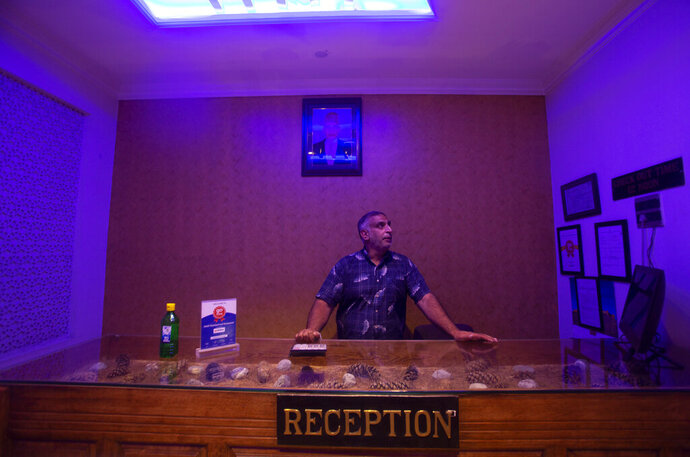 Kashmiri hotel manager Khurshid Ahmed stands at the reception counter of Hotel Standard during lockdown to stop the spread of the coronavirus in Srinagar, Indian controlled Kashmir, July 15, 2020. The seven-decades old hotel had a staff of 30 but now they're down to just three, according to Khurshid. The only activity inside the once-bustling place is by the cleaning staff. Indian-controlled Kashmir's economy is yet to recover from a colossal loss a year after New Delhi scrapped the disputed region's autonomous status and divided it into two federally governed territories. (AP Photo/Mukhtar Khan)