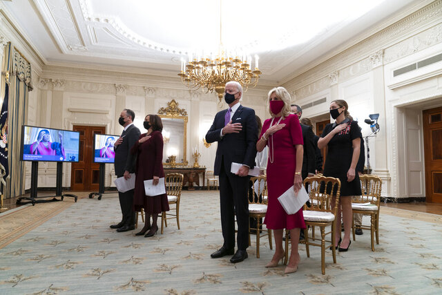 Doug Emhoff, left, Vice President Kamala Harris, President Joe Biden, and first lady Jill Biden, stand during a performance of the national anthem during a virtual Presidential Inaugural Prayer Service, in the State Dinning Room of the White House, Thursday, Jan. 21, 2021, in Washington. (AP Photo/Alex Brandon)