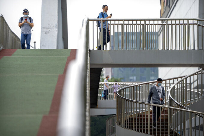 People wearing face masks to protect against COVID-19 walk across a pedestrian bridge during the morning rush hour in Beijing, Wednesday, Aug. 4, 2021. China's worst coronavirus outbreak since the start of the pandemic a year and a half ago escalated Wednesday with dozens more cases around the country, the sealing-off of one city and the punishment of its local leaders. (AP Photo/Mark Schiefelbein)