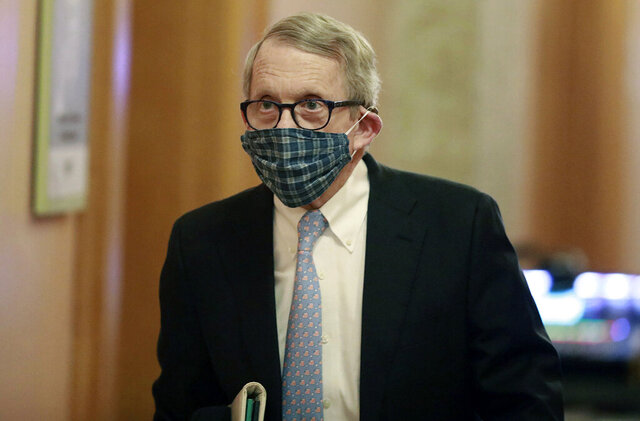 FILE - In this April 16, 2020, file photo wearing his protective mask made by his wife, Ohio Gov. Mike DeWine walks into his daily coronavirus news conference at the Ohio Statehouse in Columbus, Ohio. DeWine, a Republican who has earned praise for aggressive measures to curb the spread of the coronavirus, used the phrase