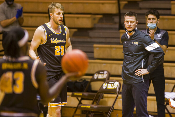 Valparaiso head coach Matt Lottich, front right, looks on as players Sheldon Edwards (13) and Ben Krikke (23) come off the court for a timeout during the second half of an NCAA college basketball game against Drake, Sunday, Feb. 7, 2021, in Valparaiso, Ind. (AP Photo/Robert Franklin)