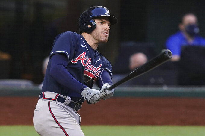 """FILE - In this Oct. 13, 2020, file photo, Atlanta Braves' Freddie Freeman watches his two-run home run during the fourth inning in Game 2 of the baseball team's NL Championship Series against the Los Angeles Dodgers in Arlington, Texas. Freeman easily won the NL MVP award Thursday, Nov. 12, topping off a trying year that saw him become so ill with COVID-19 he prayed """"please don't take me."""" (AP Photo/Eric Gay, File)"""