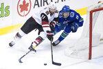 Vancouver Canucks' Ashton Sautner, right, checks Arizona Coyotes' Derek Stepan during the second period of an NHL hockey game Thursday, Feb. 21, 2019, in Vancouver, British Columbia. (Darryl Dyck/The Canadian Press via AP)