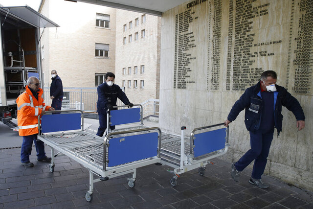 Personnel carry new beds inside the hospital of Codogno, near Lodi in Northern Italy, Friday, Feb. 21,2020. Health officials reported the country's first cases of contagion of COVID-19 in people who had not been in China. The hospital in Codogno is one of the hospitals - along with specialized Sacco Hospital in Milan - which is hosting the infected persons and the people that were in contact with them and are being isolated. (AP Photo/Luca Bruno)