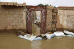 A man sets out sandbags to try to keep floodwaters from entering a house in the town of Shaqilab, about 15 miles (25 km) southwest of the capital, Khartoum, Sudan, Monday, Aug. 31, 2020. (AP Photo/Marwan Ali)