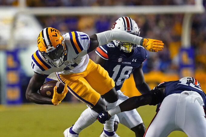 LSU wide receiver Brian Thomas Jr. (11) carries against Auburn cornerback Nehemiah Pritchett (18) and Auburn safety Zion Puckett in the first half of an NCAA college football game in Baton Rouge, La., Saturday, Oct. 2, 2021. (AP Photo/Gerald Herbert)