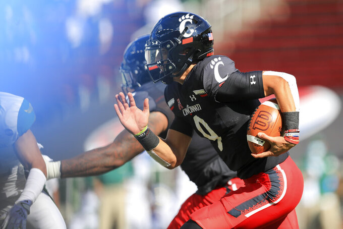 Cincinnati's Desmond Ridder carries the ball during the first half of an NCAA college football game against South Florida, Saturday, Oct. 3, 2020, in Cincinnati. (AP Photo/Aaron Doster)