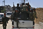 Syrian police units wave and give the victory sign as they patrol in the town of Douma, the site of a suspected chemical weapons attack, near Damascus, Syria, Monday, April 16, 2018. Faisal Mekdad, Syria's deputy foreign minister, said on Monday that his country is