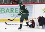 Minnesota Wild's Luke Kunin, left, reaches for the puck, leaving Colorado Avalanche's Ryan Graves behind on the ice in the first period of an NHL hockey game Thursday, Nov 21, 2019, in St. Paul, Minn. (AP Photo/Jim Mone)