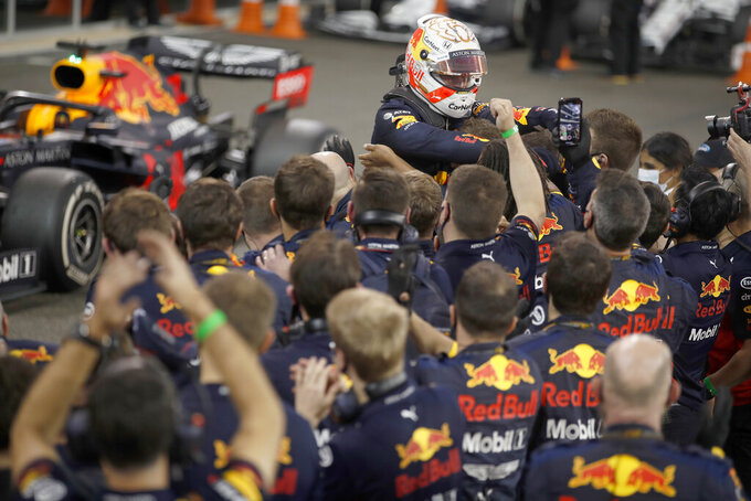Red Bull driver Max Verstappen of the Netherlands celebrates his victory with his team during the Formula One race at the Yas Marina racetrack in Abu Dhabi, United Arab Emirates, Sunday, Dec.13, 2020. (Hamad Mohammed, Pool via AP)