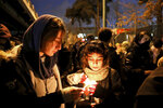 People gather for a candlelight vigil to remember the victims of the Ukraine plane crash, at the gate of Amri Kabir University that some of the victims of the crash were former students of, in Tehran, Iran, Saturday, Jan. 11, 2020. Iran on Saturday, Jan. 11, acknowledged that its armed forces