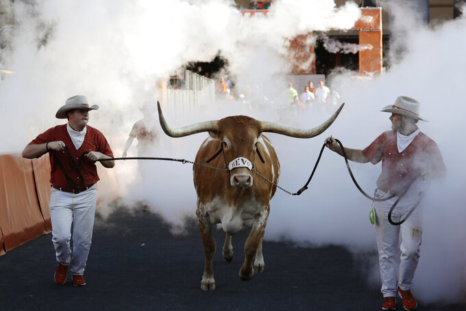 Texas mascot Bevo runs on the field before an NCAA college football game between Texas and LSU, Saturday, Sept. 7, 2019, in Austin, Texas. Football is being played in the Power Five conferences, but many of the longstanding traditions that go along with the games are on hold during the coronavirus pandemic. (AP Photo/Eric Gay)