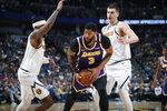 Los Angeles Lakers forward Anthony Davis, center, drives between Denver Nuggets forward Torrey Craig, left, and center Nikola Jokic during the first half of an NBA basketball game Wednesday, Feb. 12, 2020, in Denver. (AP Photo/David Zalubowski)