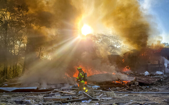 A firefighter walks through the burning rubble of a shopping center after an explosion in Harrisonburg, Va., Saturday, Oct. 17, 2020. Three people were transported for injuries from the blast. The cause of the explosion has not been released yet. (Ian Munro /Daily News-Record via AP)