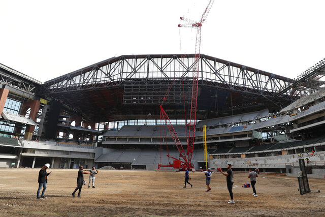 Texas Rangers players warm up during a tour of the under construction baseball field at the new Rangers stadium in Arlington, Texas, Wednesday, Dec. 4, 2019. (AP Photo/LM Otero)