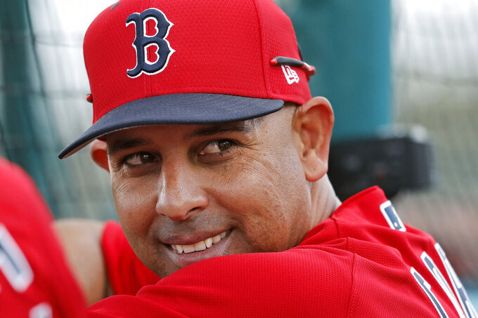 FILE - In this Feb. 18, 2019, file photo, Boston Red Sox manager Alex Cora smiles from behind the batting cage during their first full squad workout at their spring training baseball facility in Ft. Myers, Fla. The Red Sox rehired Cora as manager Friday, Nov. 6, 2020, less than a year after letting him go because of his role in the Houston Astros cheating scandal. (AP Photo/Gerald Herbert, File)