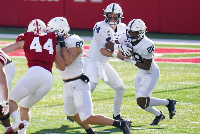 Penn State quarterback Sean Clifford (14) hands the ball off to running back Devyn Ford (28) as tight end Zack Kuntz (82) blocks Nebraska linebacker Garrett Nelson (44), during the first half of an NCAA college football game in Lincoln, Neb., Saturday, Nov. 14, 2020. (AP Photo/Nati Harnik)