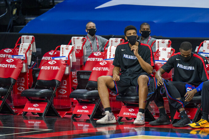 Philadelphia 76ers' Tony Bradley, left, and Paul Reed, right, look on from the bench as they are the only two players on the bench during the first half of an NBA basketball game against the Denver Nuggets, Saturday, Jan. 9, 2021, in Philadelphia. (AP Photo/Chris Szagola)