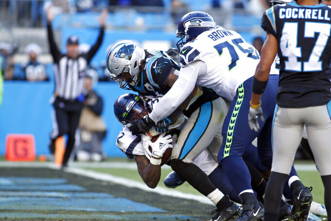 Seattle Seahawks running back Chris Carson scores a touchdown while Carolina Panthers outside linebacker Shaq Thompson (54) tackles during the second half of an NFL football game in Charlotte, N.C., Sunday, Dec. 15, 2019. Seattle Seahawks offensive tackle Duane Brown (76) assists at right. (AP Photo/Brian Blanco)