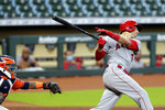 Los Angeles Angels' Jason Castro follows through on an RBI single in front of Houston Astros catcher Martin Maldonado during the fifth inning of the first game of a baseball doubleheader Tuesday, Aug. 25, 2020, in Houston. (AP Photo/Michael Wyke)
