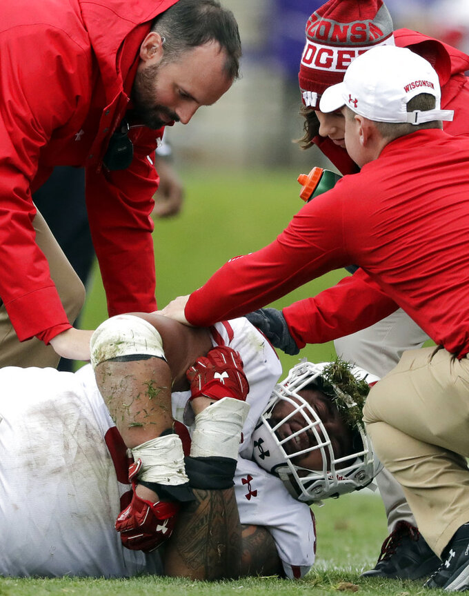Wisconsin north tackle Olive Sagapolu is helped after an injury during the second half of an NCAA college football game against Northwestern in Evanston, Ill., Saturday, Oct. 27, 2018. Northwestern won 31-17. (AP Photo/Nam Y. Huh)