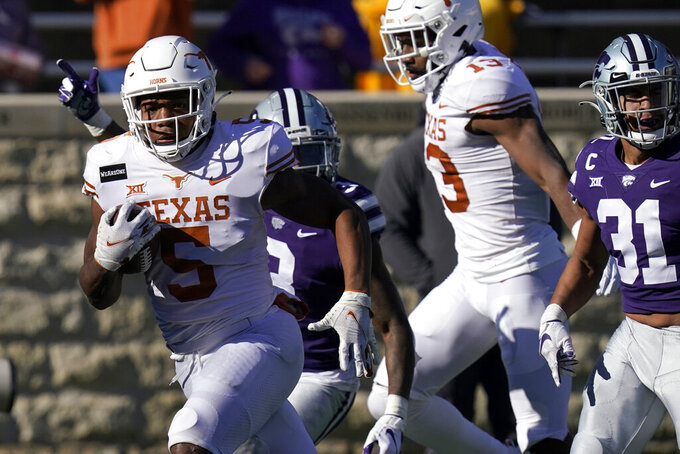 Texas running back Bijan Robinson (5) breaks free for a touchdown during the first half of an NCAA college football game against Kansas State in Manhattan, Kan., Saturday, Dec. 5, 2020. Robinson scored three touchdowns in the game. Texas defeated Kansas State 69-31. (AP Photo/Orlin Wagner)